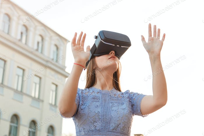 Young Woman enjoy with VR device outdoor