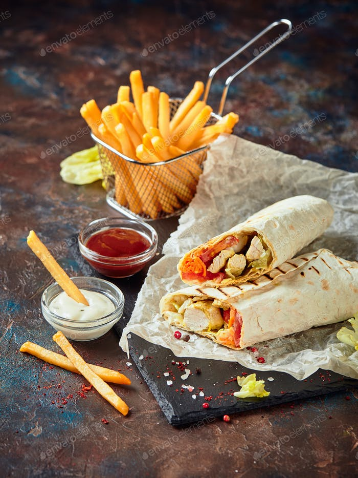 Eastern traditional shawarma, and French fries with sauces on slate
