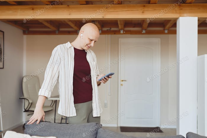 Smiling Bald Woman Using Smartphone