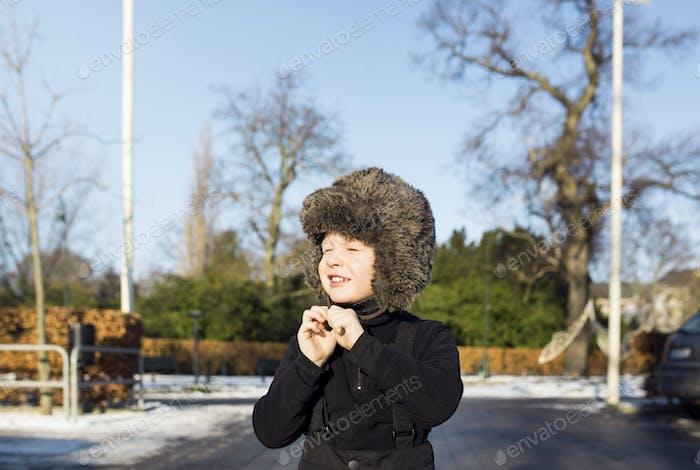 Niño con sombrero de piel en la calle durante el invierno