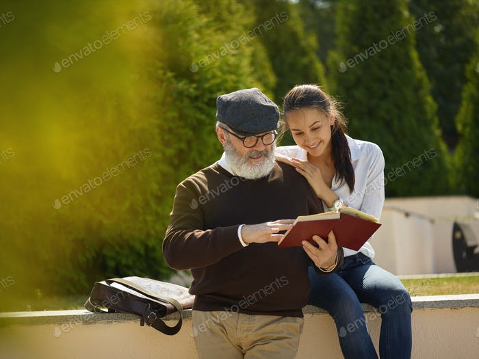 Portrait of young girl embracing grandfather at park