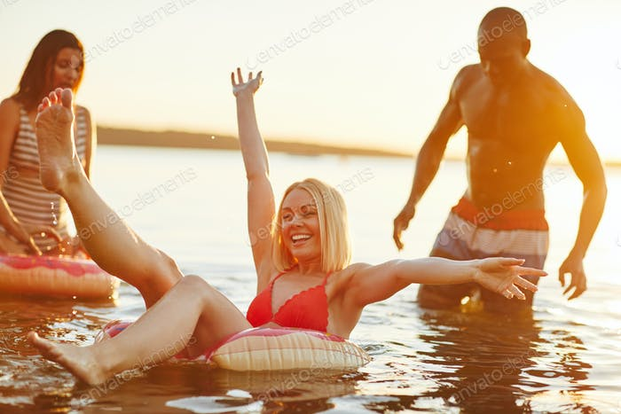 Laughing young woman floating on a lake with friends