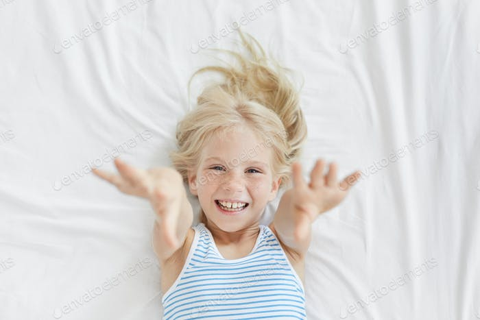 High angle view of lovely baby girl of preschool age smiling happily, reaching out hands towards cam