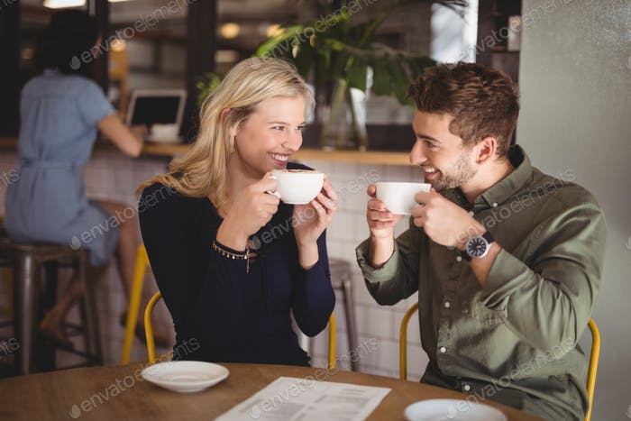 Cheerful couple drinking coffee at cafe