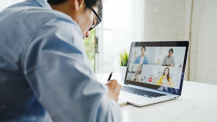 Young Asia businessman using laptop talk to colleagues in video call meeting at living room.