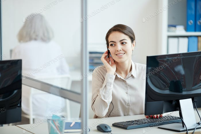 Smiling Female Secretary Wearing Headset at Workplace