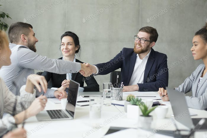 Boss shaking hands with employee at meeting