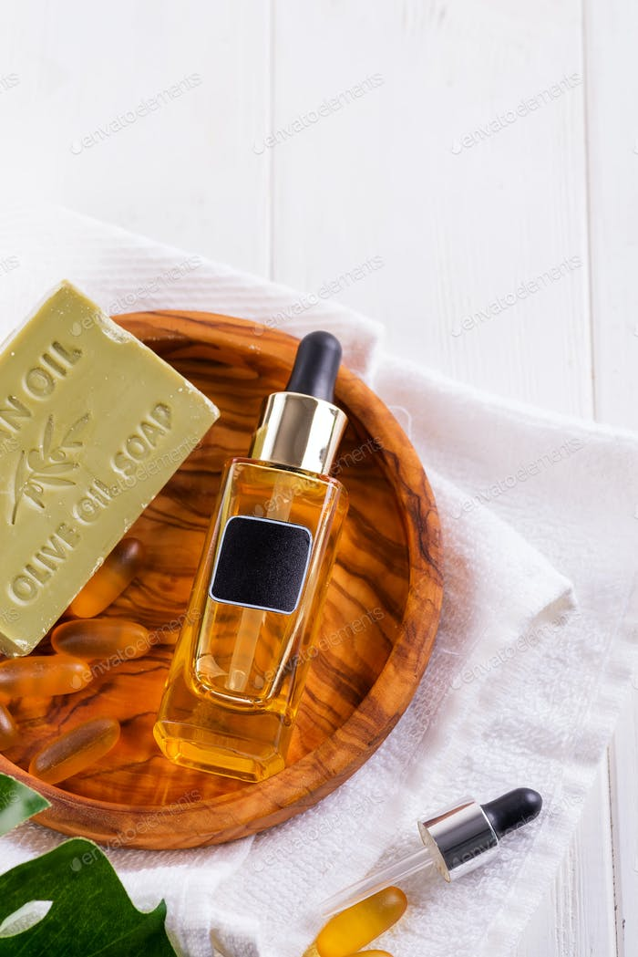 Cosmetic bottle with serum or hyaluronic acid and olive soap, Omega-3 gel capsules on wooden plate