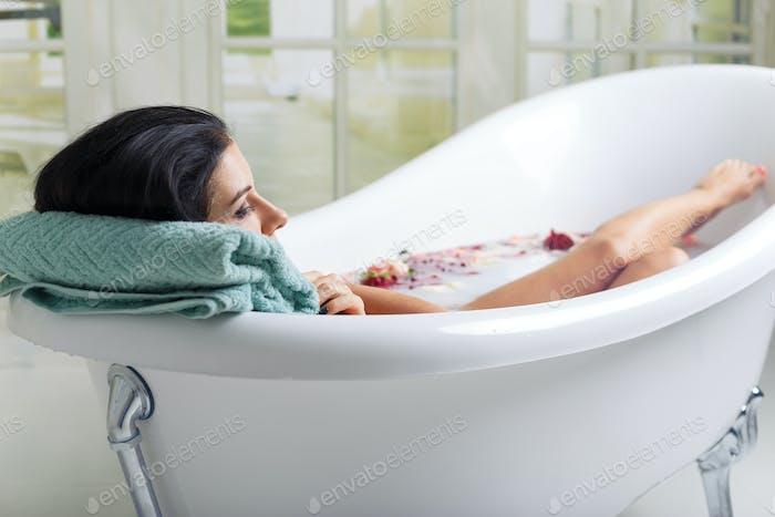 beautiful young woman takes milk bath
