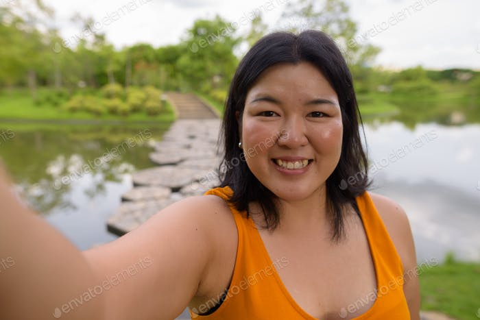 Personal point of view of beautiful overweight woman taking selfie in park
