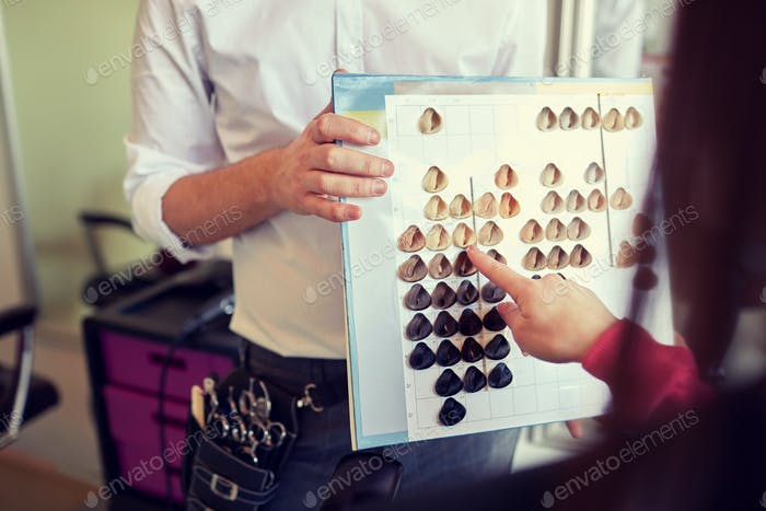 woman choosing hair color from palette at salon