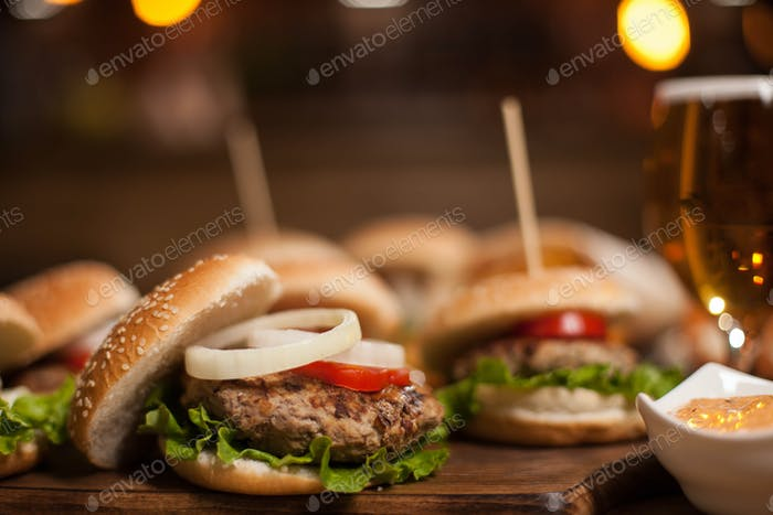 Closeup of homemade burgers on wooden cutting board