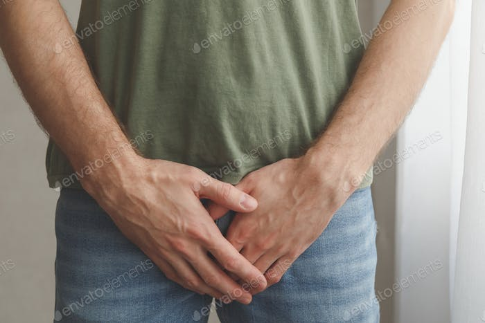 Man cover his groin by hands. Men's health. Urology problems male