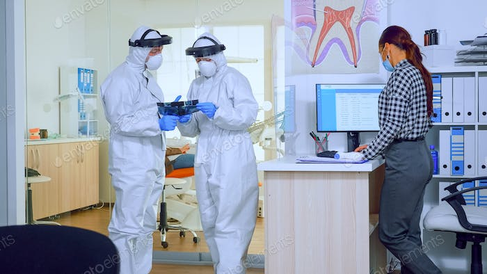 Orthodontics doctors with face shield and ppe suit discussing