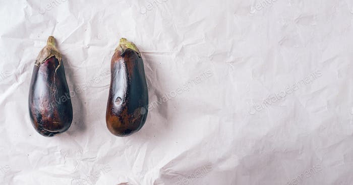 Rotten eggplant on craft paper background. Concept of zero waste production. Top view. Copy space