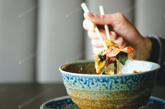 Man's hand holding chopsticks over a plate of Japanese, thai, chinese meal - rice, mushroom