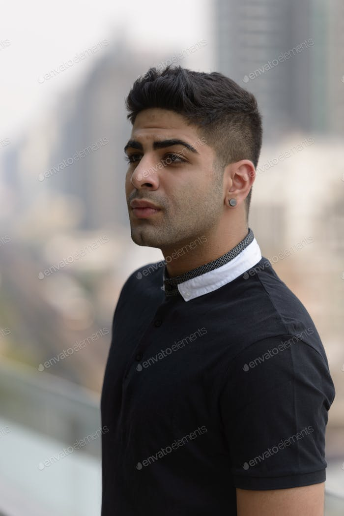 Portrait of young handsome Indian man in the city