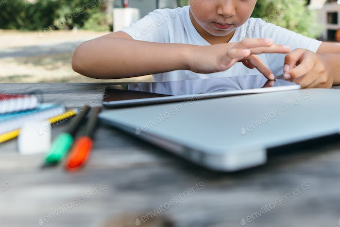 Crop child browsing tablet in garden