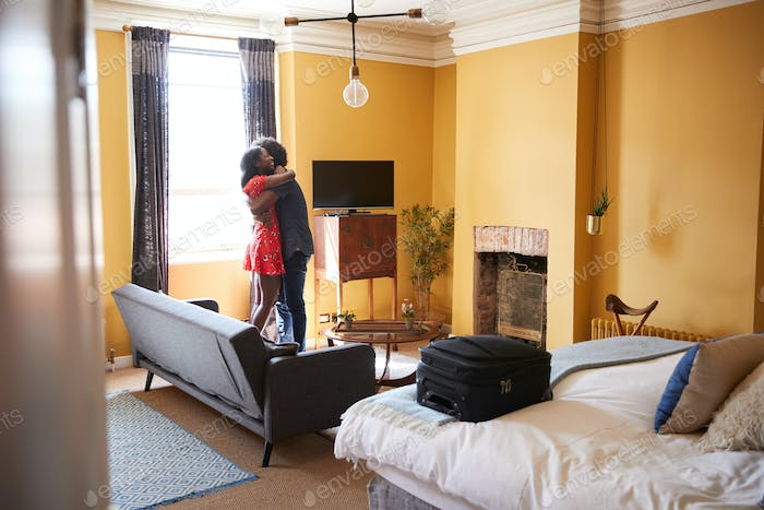 Black couple embracing in a hotel room, full length