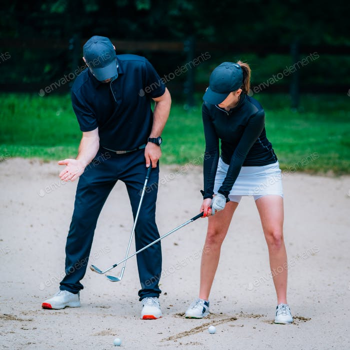 Golf sand bunker playing technique. Young woman practicing bunker shots with golf instructor