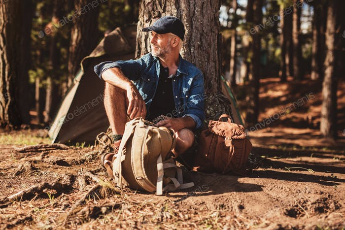 Mature man sitting alone at campsite with backpack
