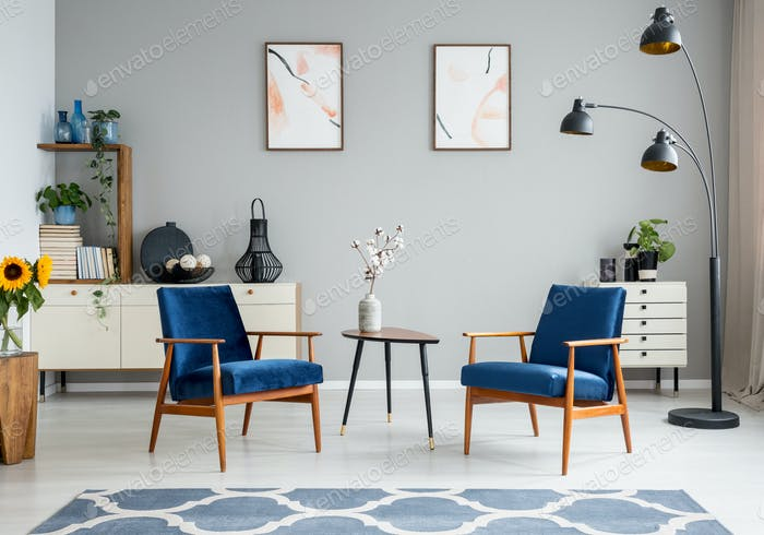 Flowers on wooden table between blue armchairs in living room in