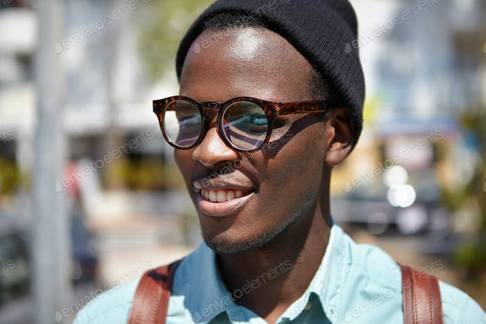 Close up summer portrait of handsome cheerful young black European student in trendy eyewear and hat