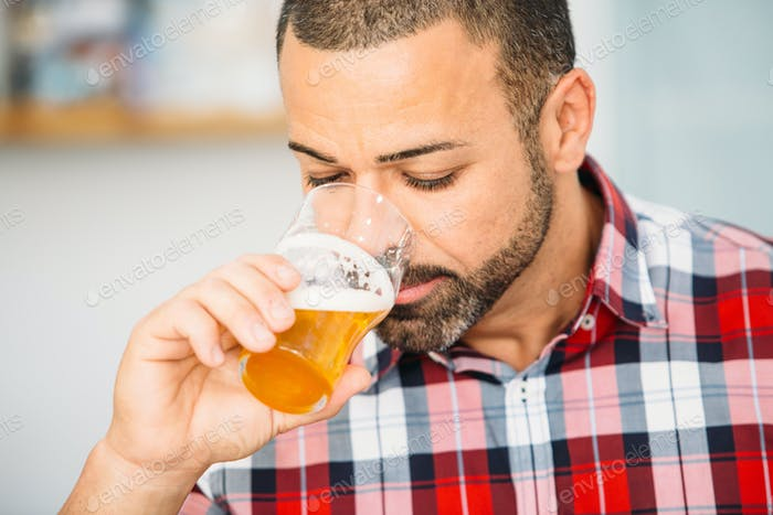 Bearded man smelling craft beer