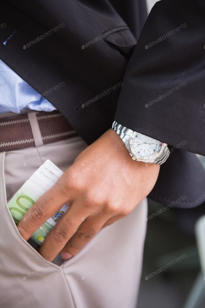 Mid section of young businessman keeping currency in pocket