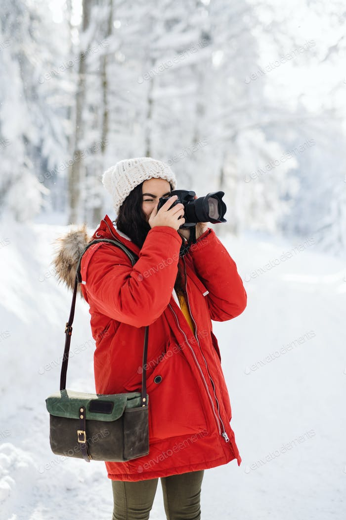 Young woman with camera standing outdoors in snow in winter forest, taking photos