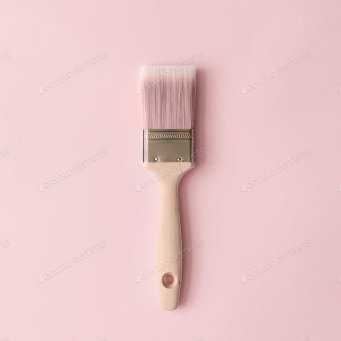 Creative concept made with paint brush and pastel pink background. Minimal flat lay.