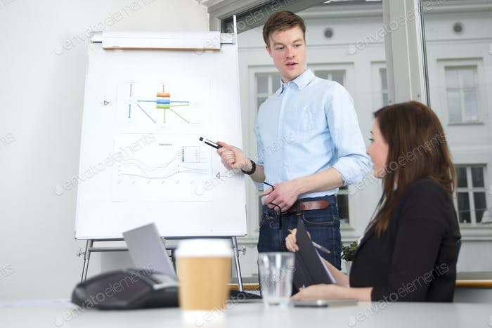 Confident Businessman Giving Presentation To Colleague In Office