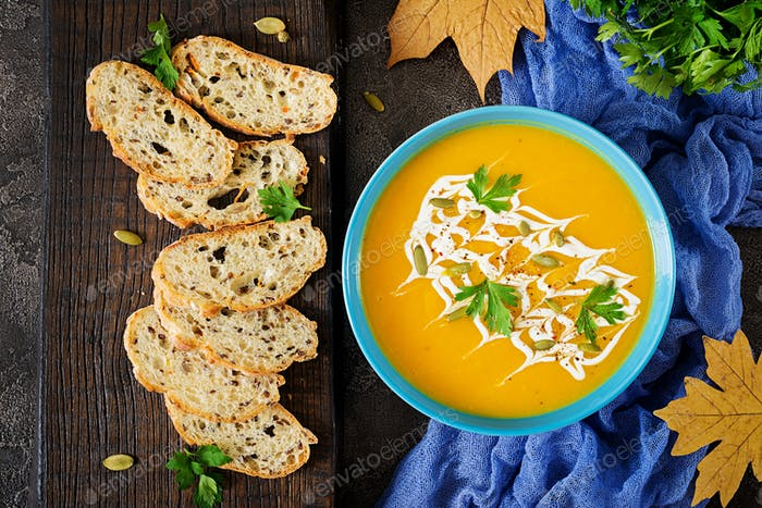 Pumpkin soup in a bowl served with parsley  and pumpkin seeds.