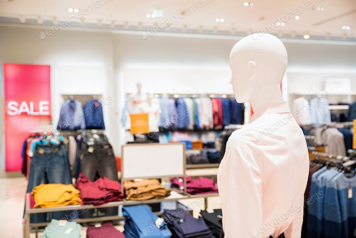 White mannequin in clothes shop with blurred interior background