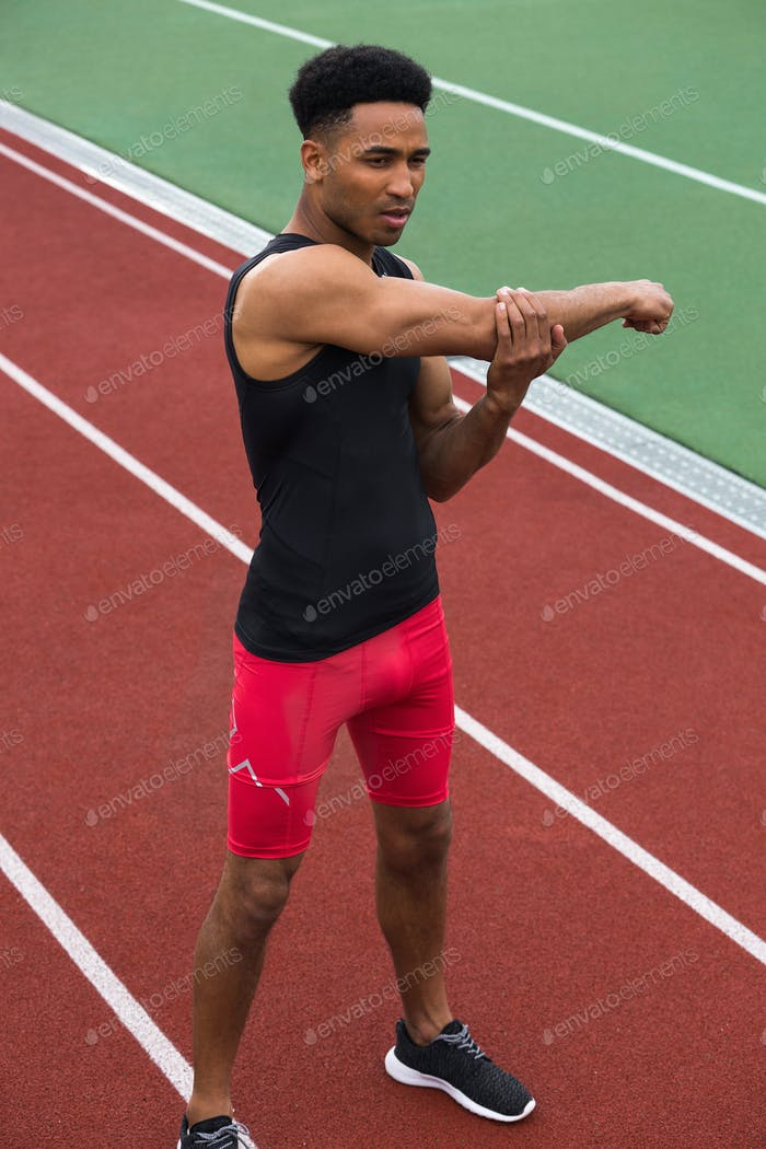 Concentrated african athlete man make stretching exercises