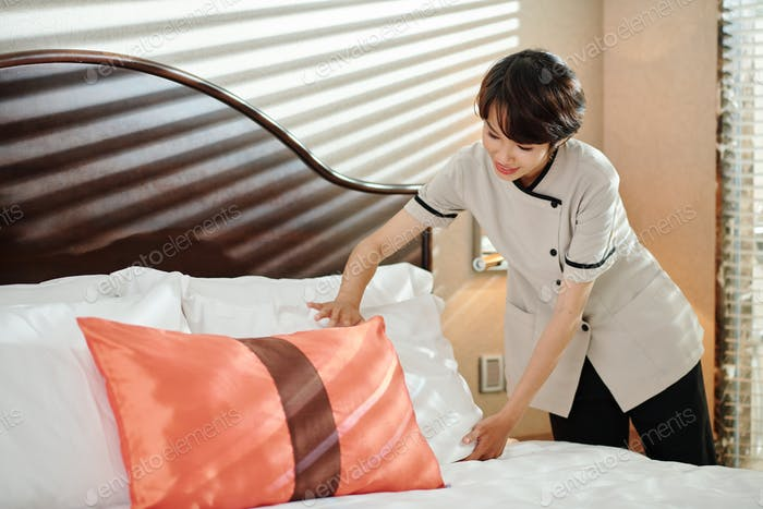 Maid adjusting pillows on be