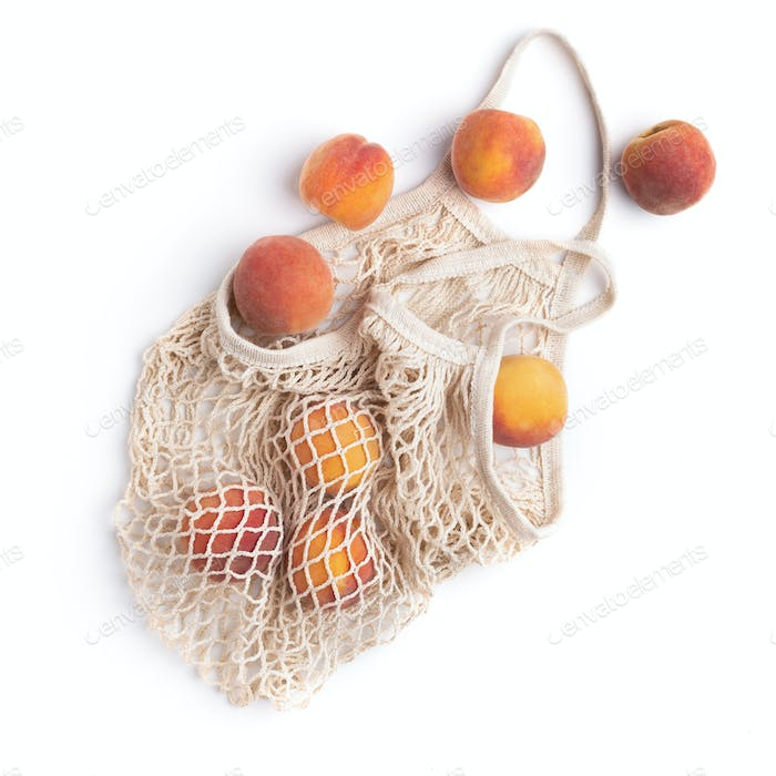 Fresh peaches inside eco net bag isolated on white