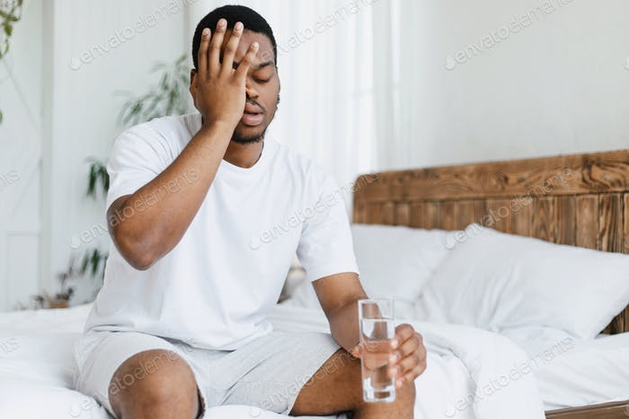 Guy Having Hangover Touching Aching Head Sitting In Bed Indoors