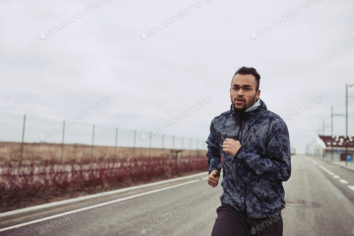 Young man in sportswear running alone along a country road