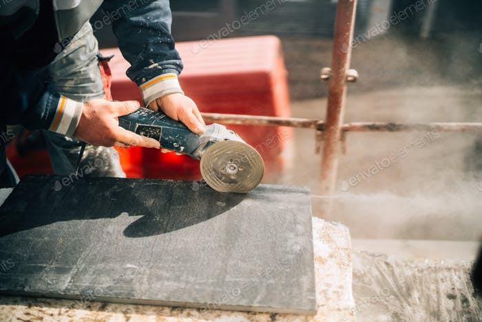 Close up details of worker cutting stone marble with angle grinder at construction site