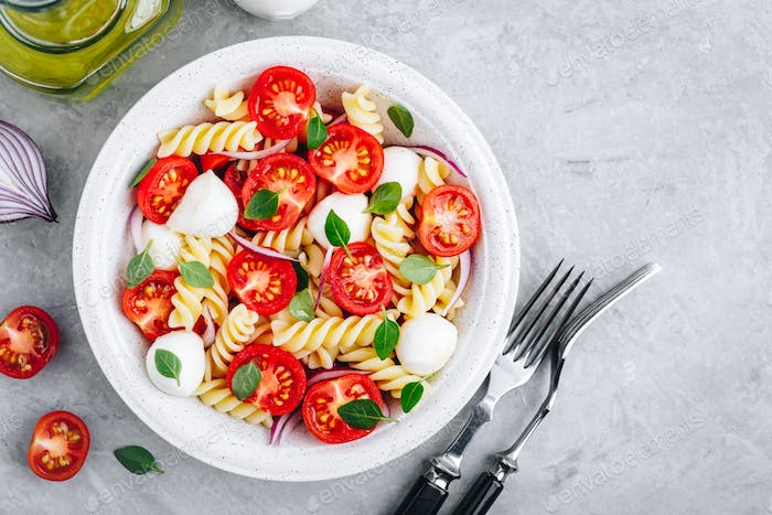 Italian pasta salad with tomatoes, mozzarella cheese, red onion and basil. Top view.