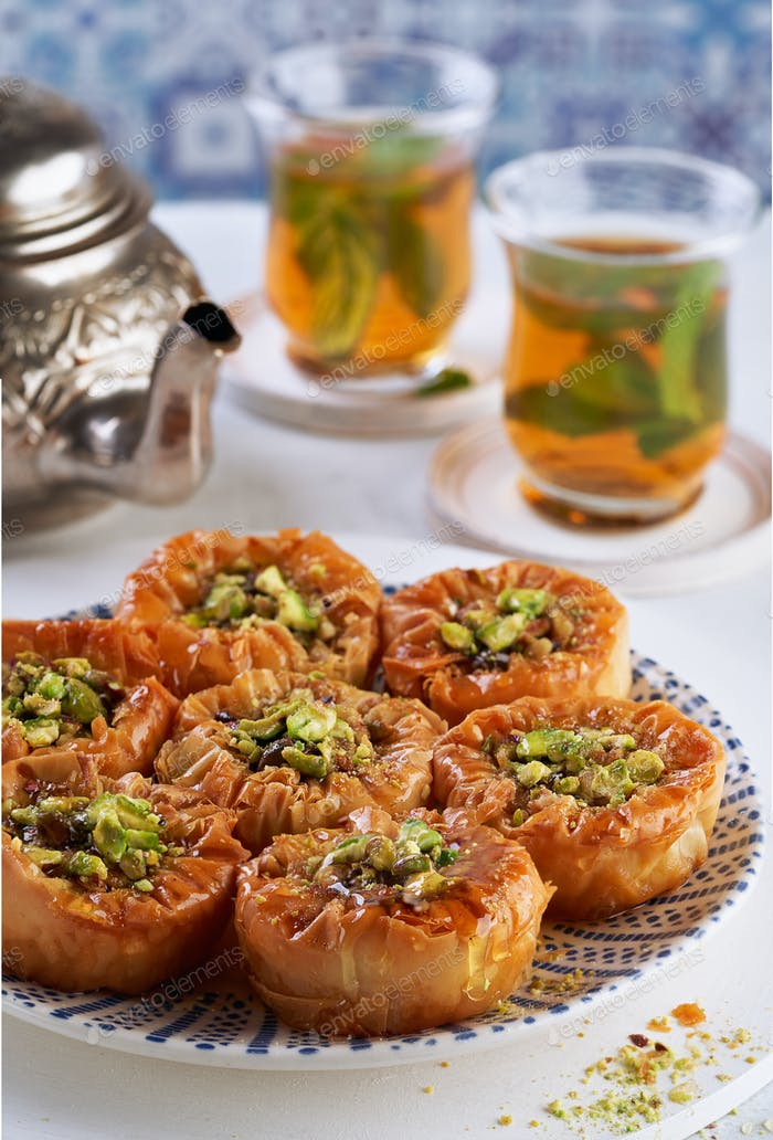 Middle eastern arab sweet pastry baklava with honey, pistachios, mint tea. Ramadan concept.