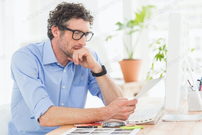A casual young businessman using computer in office
