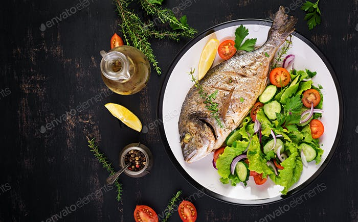Baked fish dorado with lemon and fresh salad in white plate on d