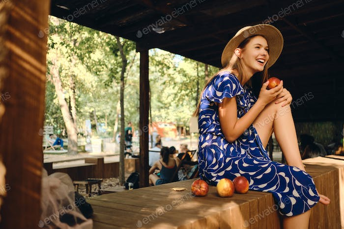 Cheerful girl in blue dress and hat barefoot eating peach happily sitting on wooden fence in park