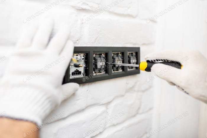 Electrician installing sockets and switches