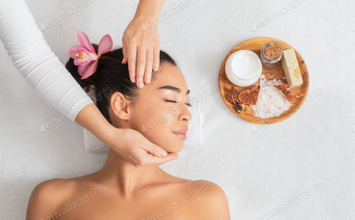 Spa Treatment. Relaxed Asian Lady Enjoying Face Massage And Aromatherapy In Salon