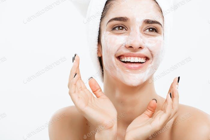 Beauty Skin Care Concept - Beautiful Caucasian Woman Face Portrait applying cream mask on her facial
