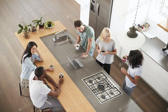 Overhead View Of Friends Drinking Coffee In Modern Kitchen