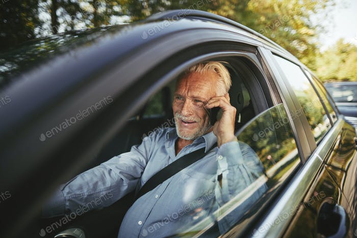 Smiling senior man talking on his cellphone in a car